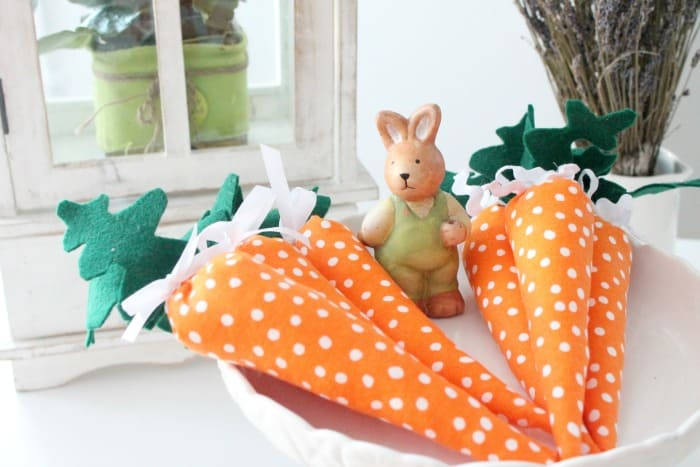Handmade stuffed carrots with belt leaves and cute polka dots. A cute Easter craft.