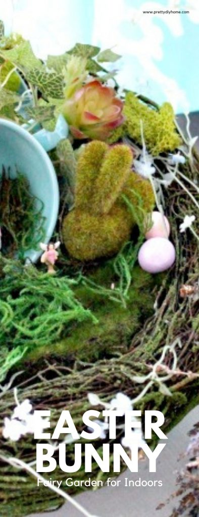 An moss covered Easter Bunny and tea cup sitting on a faux birdnest surrounded by Easter eggs for a DIY Easter Bunny fairy garden idea for indoors.
