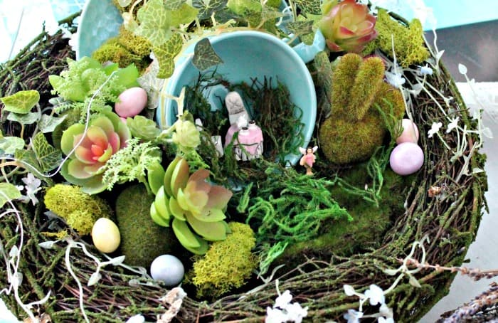 Closeup of a teacup DIY fairy garden, with a tiny table set and a Easter bunny. A fun Easter craft with a little moss Easter bunny