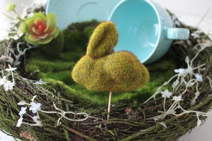 A faux moss covered miniature Easter bunny as part of a DIY indoor fairy garden or Easter centerpiece