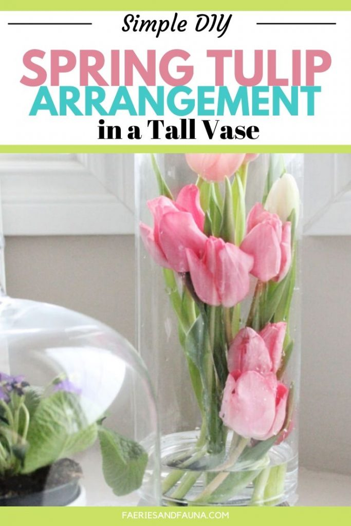 Pink tulips arranged inside a tall vase in a simple, modern and elegant tulip arrangement.