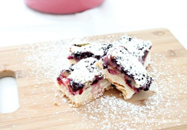 Lemon squares with blueberries and icing sugar sprinkles, cut and ready for serving.