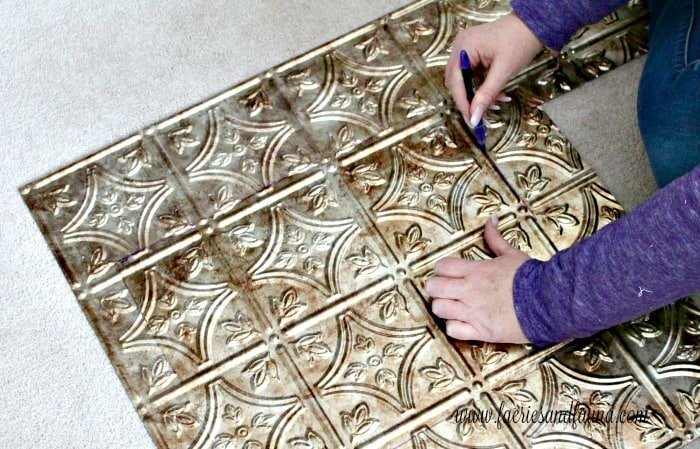 Cutting faux tin panels to fill in glass doors on a DIY living room storage solution idea.