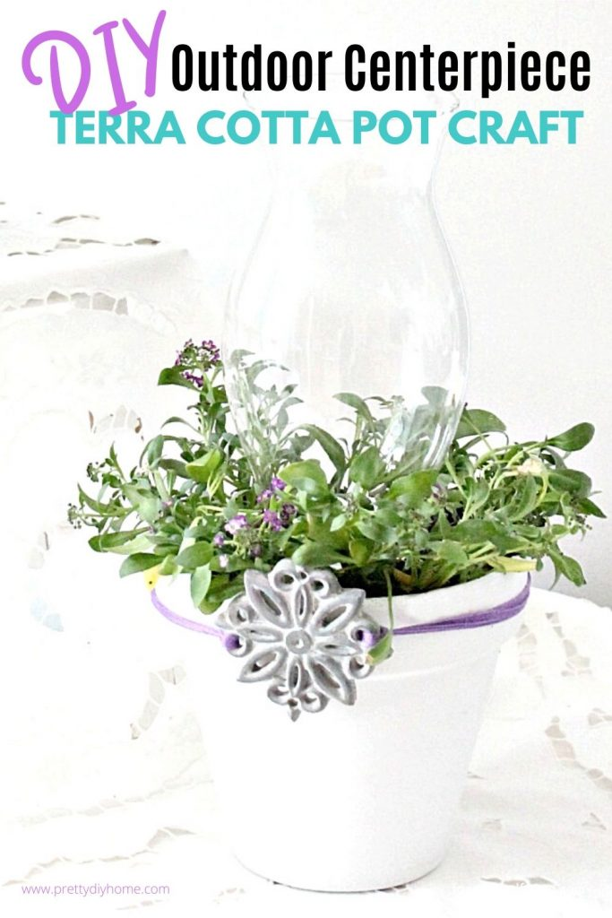 A Dollar store clay pot is painted white and given a glass lantern top with flowered plant to create an outdoor centerpiece.
