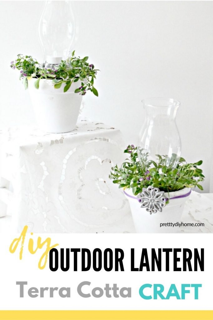 A set of white DIY lanterns made using dollar store clay pots, white paint, glass lantern covers and real plants.