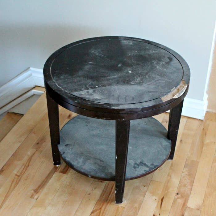 A thrift store table with damage that will be used to make a DIY wire laundry hamper with casters.