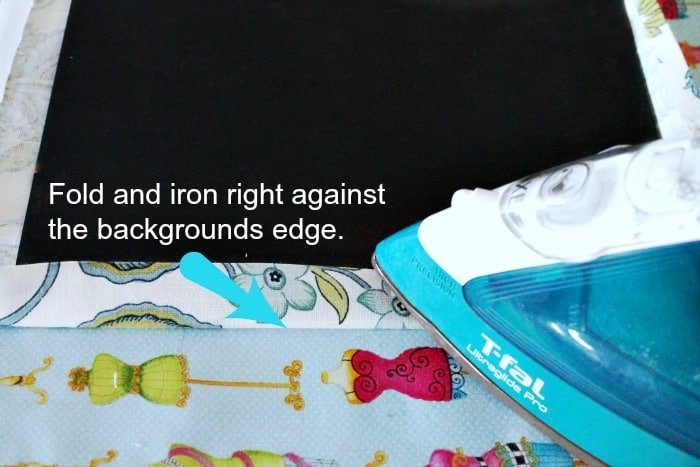 Folding and ironing fabric for a DIY Ironing board holder on a budget.
