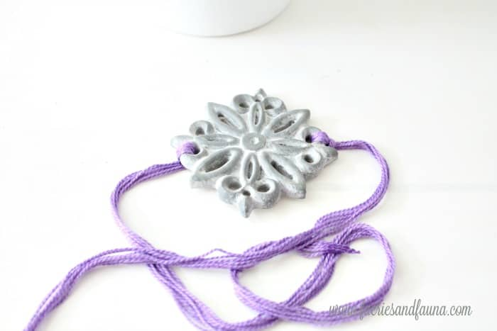 A concrete medallion and embroidery thread for attaching to a painted terra cotta pot idea.