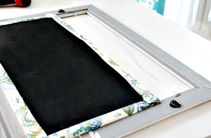 Adding a fabric cover to a frame for a DIY fabric covered ironing board holder.