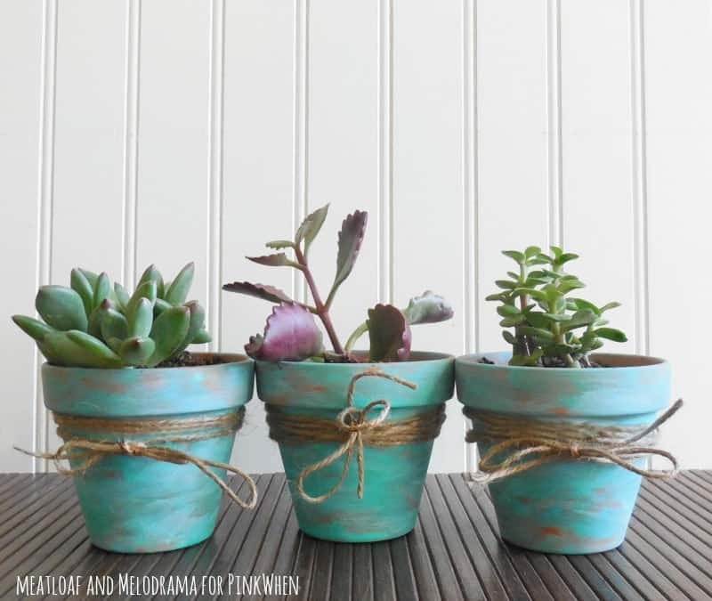 Rustic terra cotta pots decorated with turquoise paint and burlap.