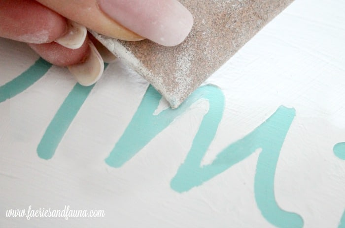 Sanding bleed through on a turquoise letter in a diy wood sign project.