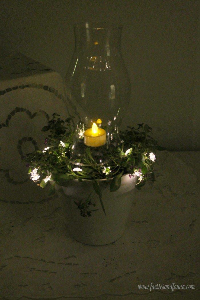 A terra cotta pot craft using chalk paint, mini lights and flowers to make a pretty flower pot lantern.