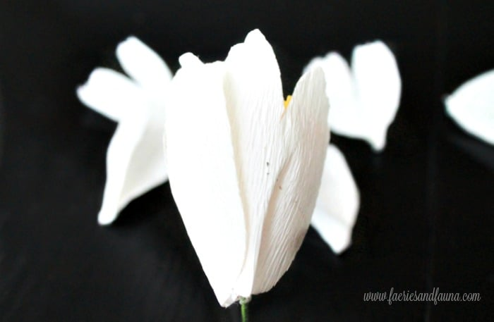 Placement of small petals around the center portion of a hand made crepe paper flower.A tutorial for paper flower crafts and a minimalist wreath craft.