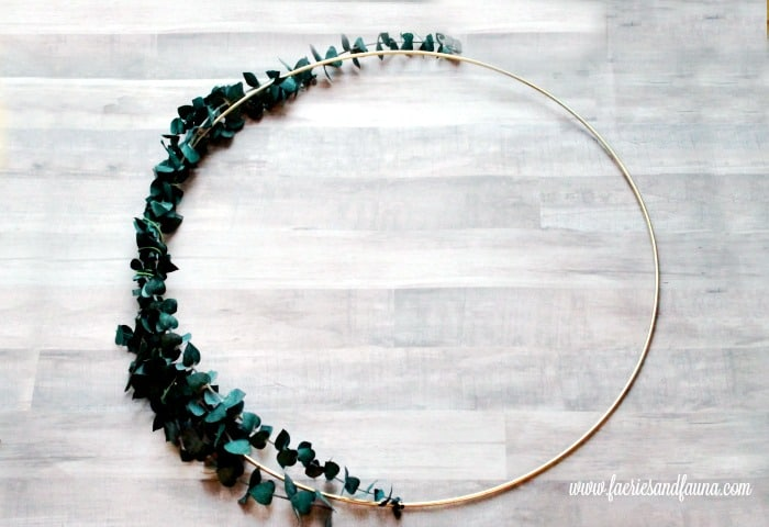 Large metal ring wreath, with eucalyptus branches, before receiving a crepe paper peony arrangement. Flower making, how to make paper flowers, flower making with crepe paper, minimalist wreath, elegant wreath, diy wedding decor, paper flowers wedding.