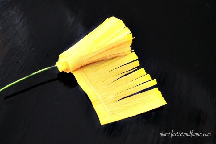 Finishing the center portion of a crepe paper flower. How to make large paper flowers with crepe paper and book pages.