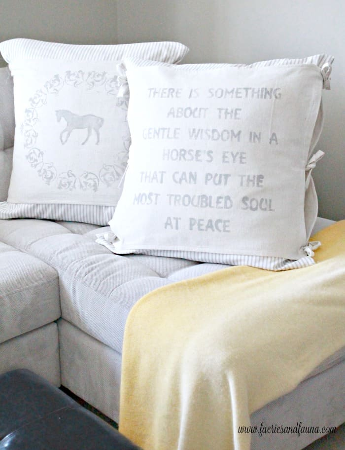 Two large DIY farmhouse cushions made with drop cloth and sewn like a banner.