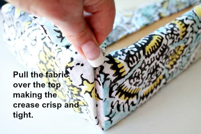 Pulling the corner tight to make a crisp line on the corner of a fabric covered valance for a holiday trailer.