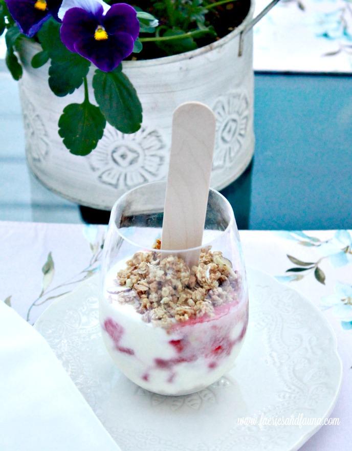 A single serving of a No bake dessert parfait with strawberries, yogurt vodka, cream cheese, and granola.