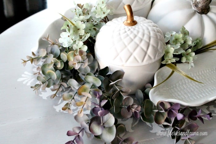 A fall decor tutorial showing flower placement on a DIY fall table centerpiece.