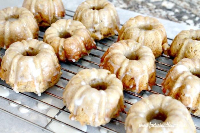 Pumpkin donuts being glazed as part of a pumpkin donut recipe.