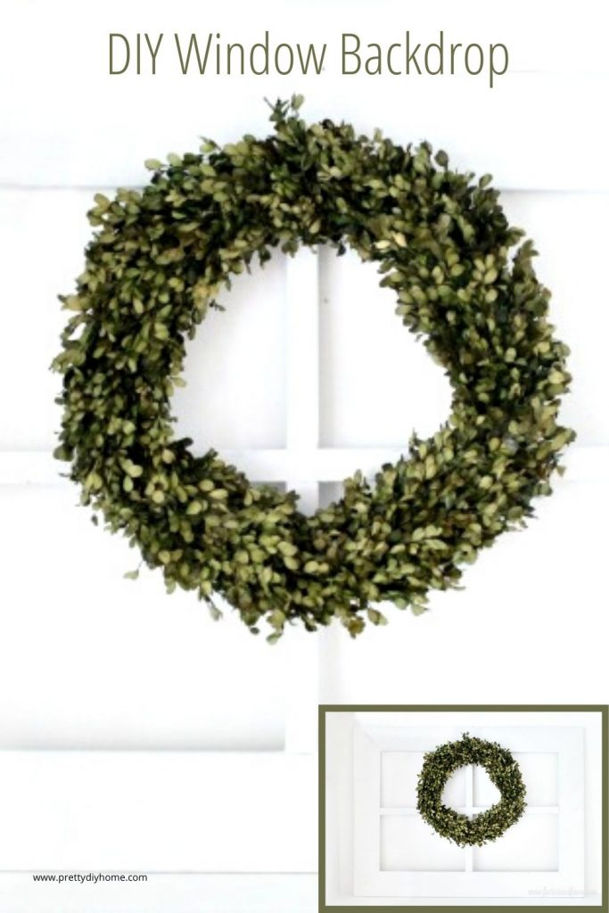 An handmade wooden window frame for farmhouse decor with a large green wreath.