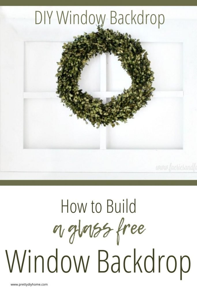 A large white wood DIY window frame backdrop in white with a minimalist green wreath.