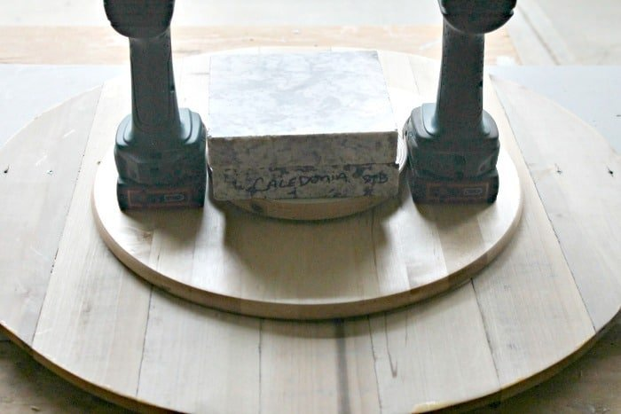 Attaching a DIY top to an existing lazy susan using glue.