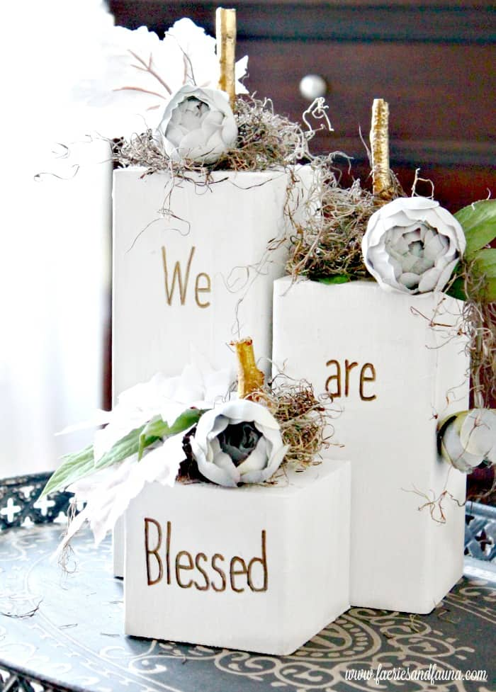 "Wood pumpkins with floral arrangements, that say ""We are Blessed"""