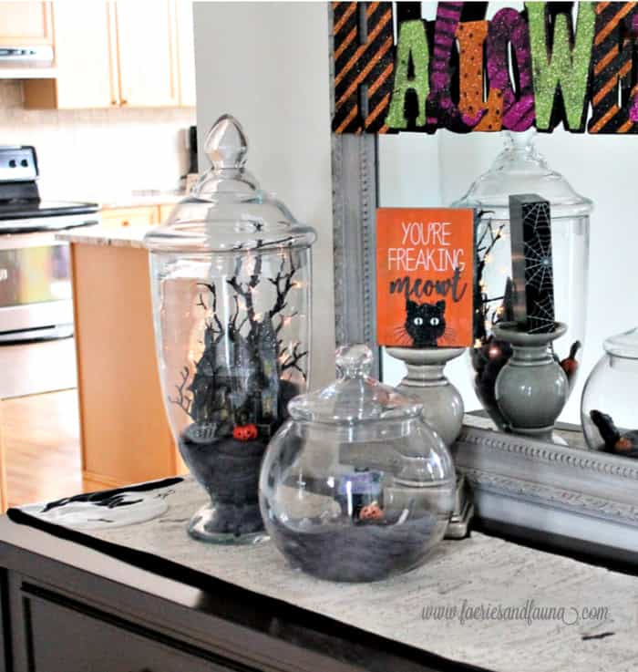 A front foyer decorated for Halloween with pretty Halloween Apothecary jars.