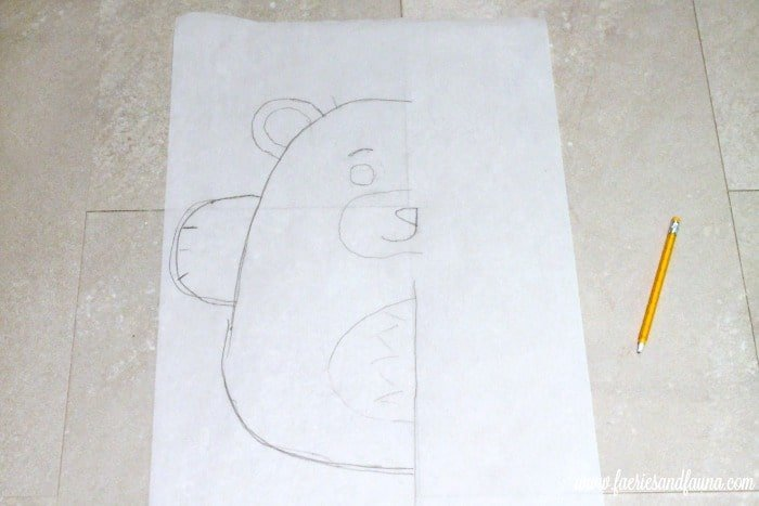 Transferring a Teddy bear DIY cushion pattern to parchment paper.