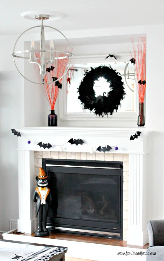 DIY Halloween mantel with easy Halloween crafts including a Halloween wreath, Halloween branches, and Halloween banner.