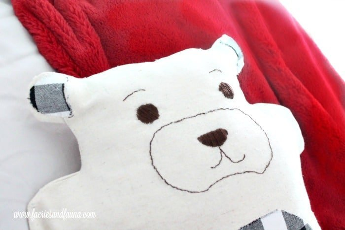 Embroidery on a little teddy bear DIY cushion for a child's bedroom at Christmas.