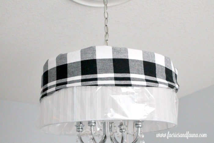 DIY lampshade in black and white buffalo check being placed on a lamp for Christmas decor.