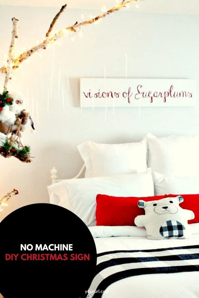 White and red sign hanging over a bed in a child's bedroom.
