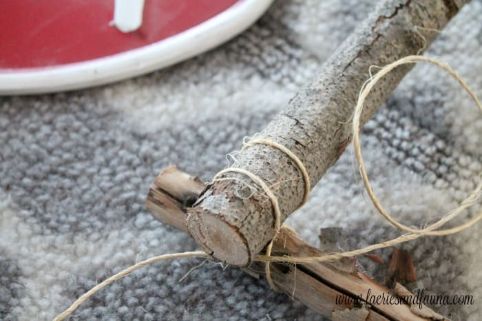 Tying knots to hold together branches on a DIY white birch wreath.