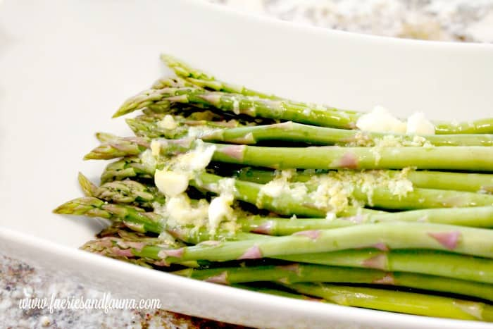 Marinating asparagus in butter, garlic and lemon zest for making Christmas appetizers