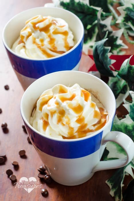 Two mugs of homemade hot chocolate with whipped cream and caramel topping.