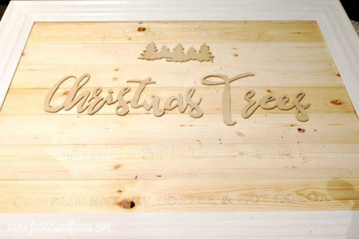 Lining up the elements on a DIY Christmas tree farm sign.