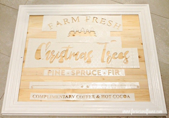 Laying out and spacing stencils for a DIY Christmas tree decor sign.