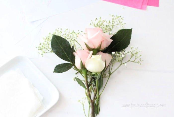 Arranging fresh cut flowers for a miniature rosebud bouquet