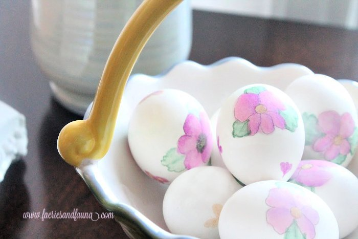 A basket of DIY watercolour floral Easter eggs.