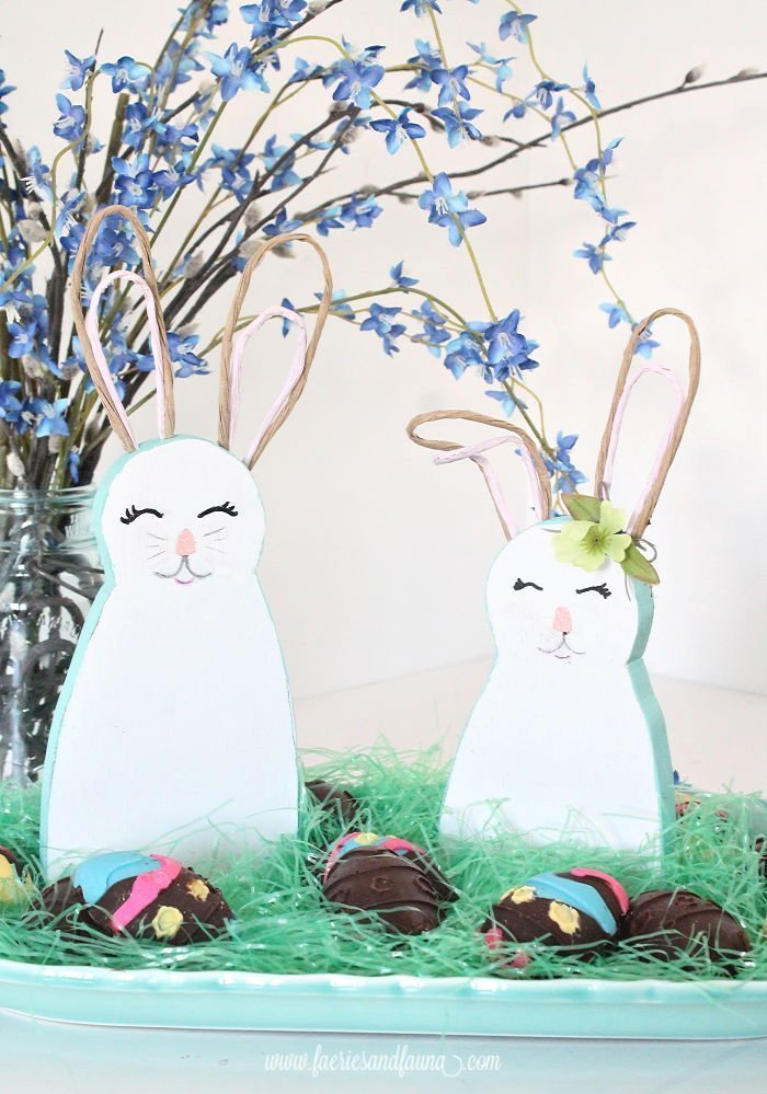Two wood bunnies with bendable wire ears, on a platter full of homemade Easter eggs.