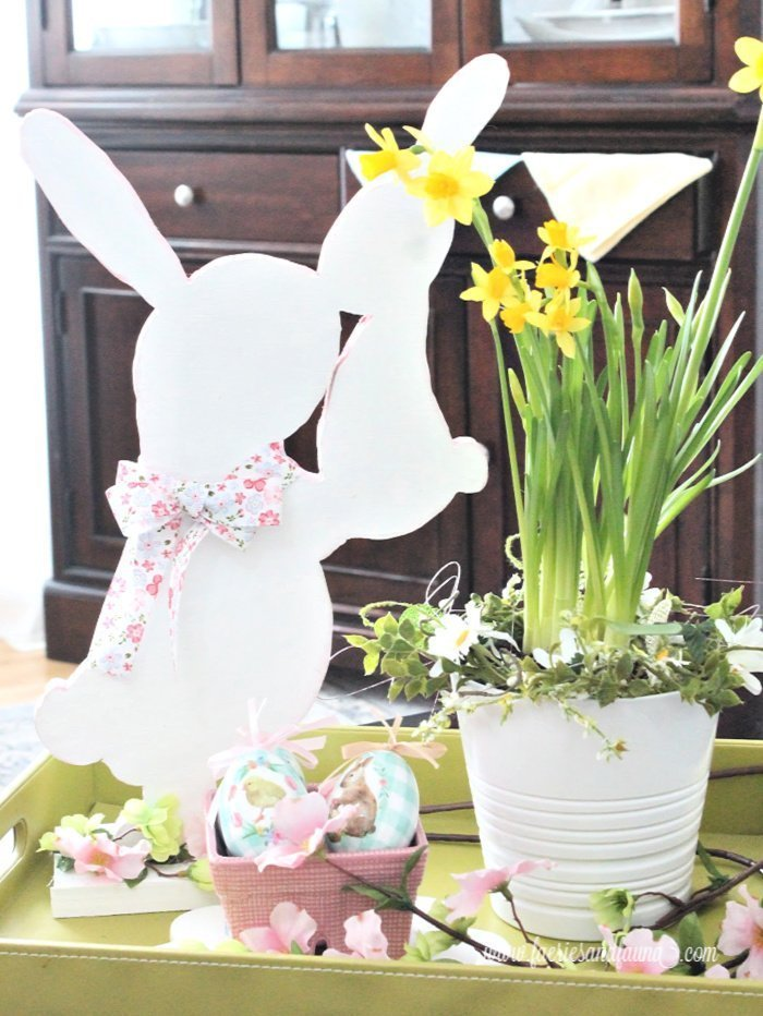 An handmade wood Easter bunny in an Easter arrangement with flowers.