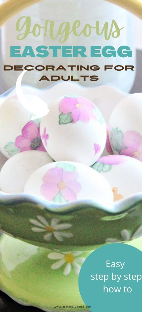 A bright green glass basket with a yellow handle full of hand painted watercolour Easter eggs with pink blossoms and green leaves.