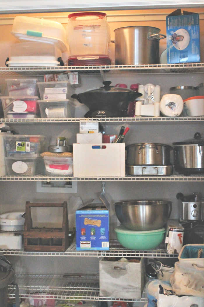 A large cupboard full of kitchen supplies and plain wire shelves.