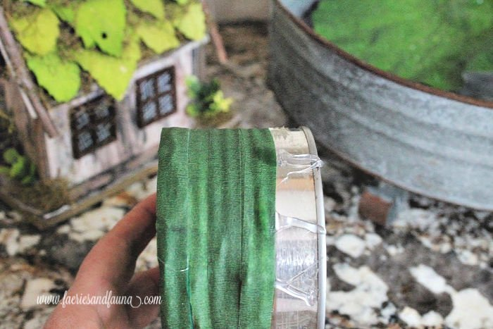 Covering a tin can for a DIY fairy garden pond craft.