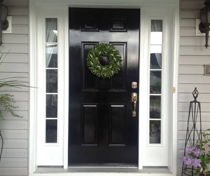 A shiny black door makeover with bright white trim.