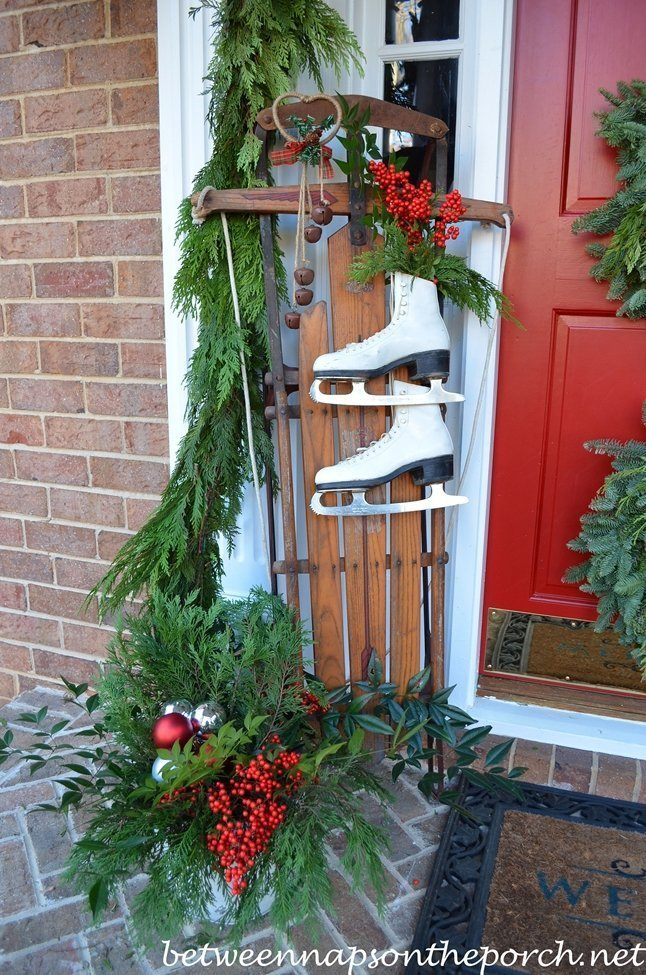 Front porch decorated with thrifted vintage toys like children's sleigh and skates.