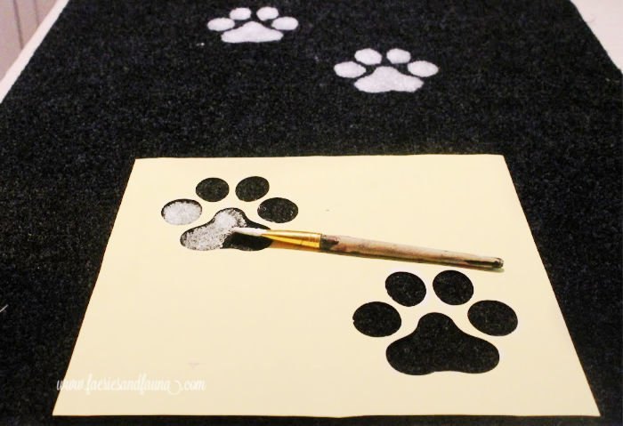 Painting paw prints onto a carpet for a DIY dog ramp