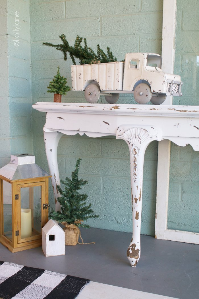 Vintage toy truck decorated for Christmas on a front porch.